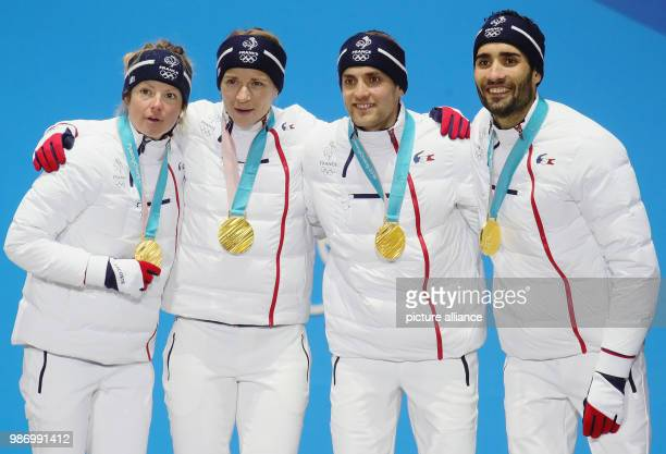 Marie Dorin Habert , Anais Bescond, Simon Desthieux and Martin Fourcade from France celebrating their gold medals on the podium during the award...