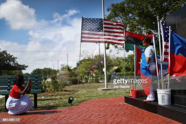 Marie Fatil takes a picture of Marie La Fortune as she holds a Haitian flag as they celebrate Haitian Flag Day in the Little Haiti neighborhood on...