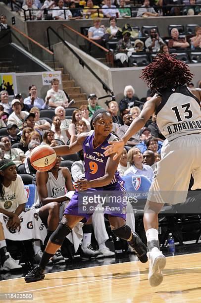 Marie FerdinandHarris of the Phoenix Mercury controls the ball against Danielle Robinson of the San Antonio Silver Stars at ATT Center on June 21...