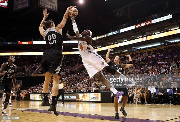 Marie FerdinandHarris of the Phoenix Mercury has her shot blocked by Ruth Riley of the San Antonio Silver Stars during the WNBA game at US Airways...