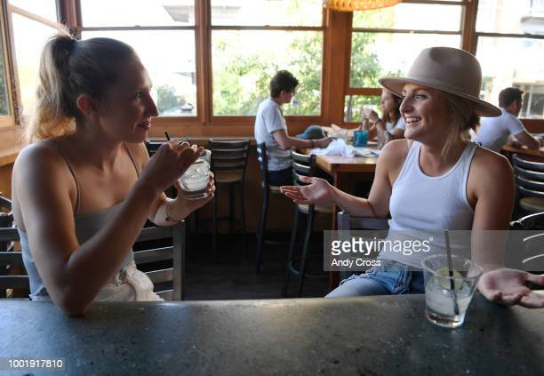 Marie Gillcrist left and Monica Hamilton right enjoy good conversation and afterwork drinks using paper straws at Lola's restaurant in Denver July 18...