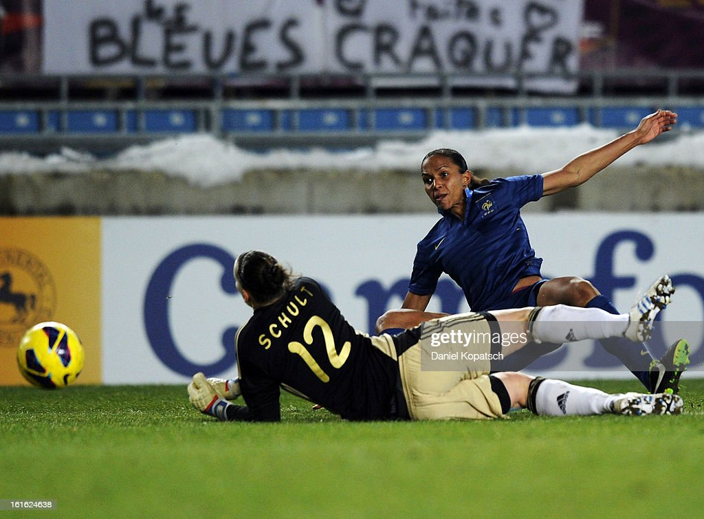 Marie Laure Delie of France (R) scores her team's third goal against Almuth Schult of Germany during the international friendly match between France and Germany at Stade de la Meinau on February 13, 2013 in Strasbourg, France.