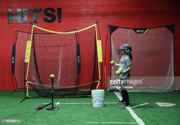 Marie Marcum holds softballs during practice with her team the Plainfield Twisters at a workout facility Saturday March 9 in Joliet Ill Marie wrote a...