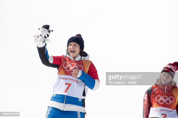 Marie Martinod of France celebrates on the podium after winning the silver medal watched by gold medalist Cassie Sharpe of Canada during the...