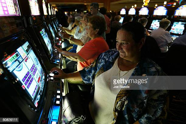 Marie Newmerer plays a slot machine May 11 2004 during the grand opening for the Seminole Hard Rock Hotel and Casino in Hollywood Florida South...