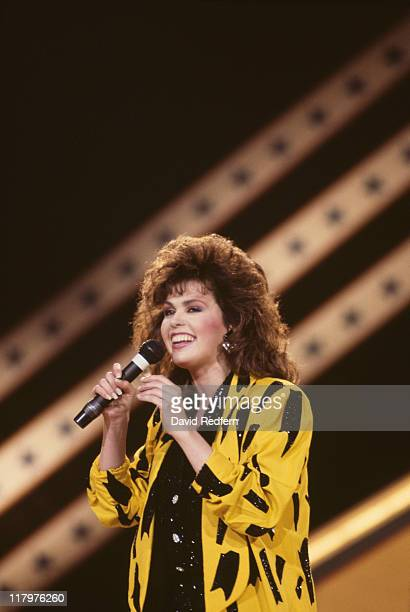 Marie Osmond US singer and musician singing into a microphone during a live concert performance on stage at the International Festival of Country...