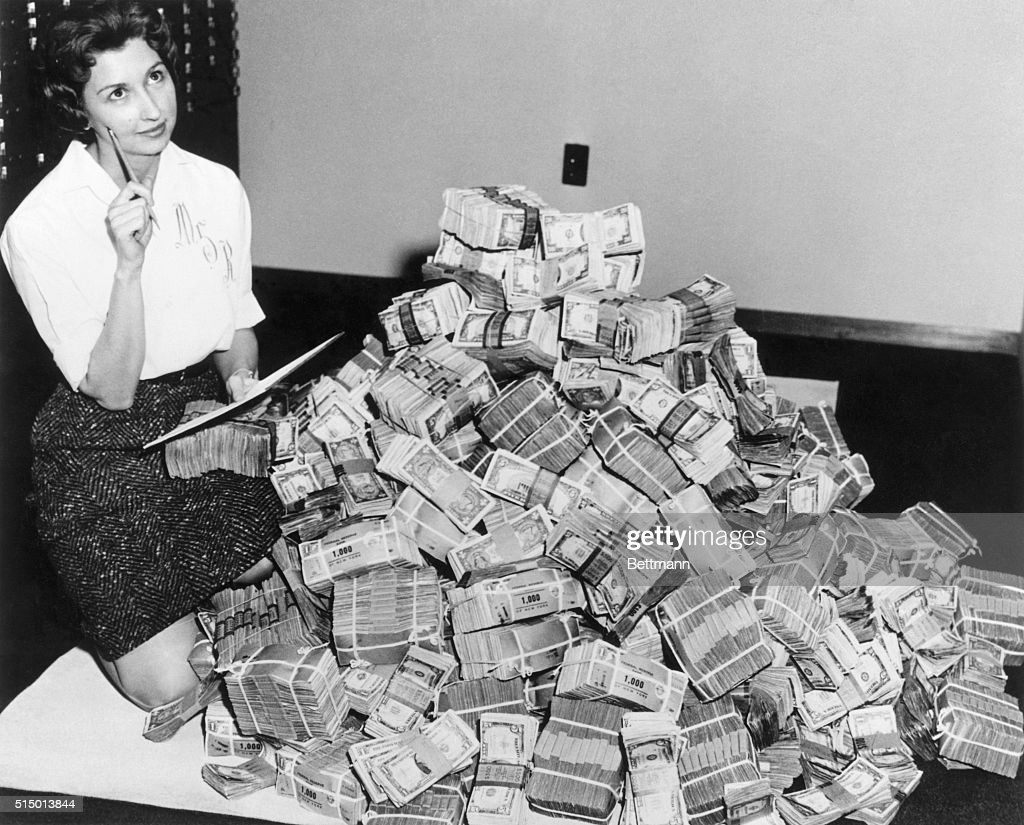 Bank Employee Sitting by a Million Dollars in Cash : News Photo