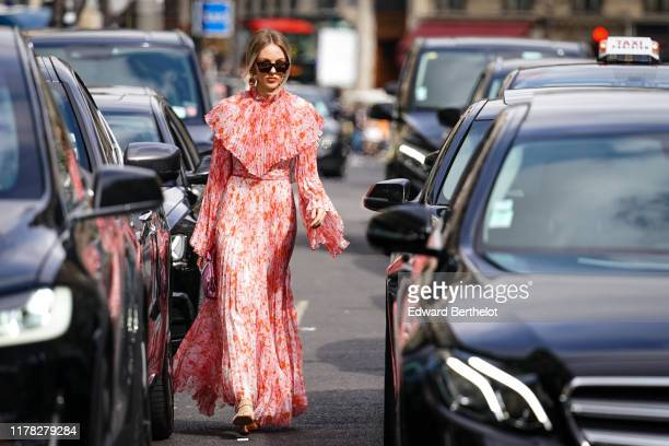 Marie Shea wears sunglasses a ruffle pleated pink and orange floral print dress a purple bag outside Giambattista Valli during Paris Fashion Week...