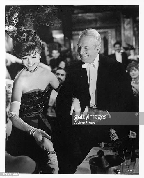 MarieHélène Arnaud smiling with Maurice Chevalier in a scene from the film 'Gigi' 1958