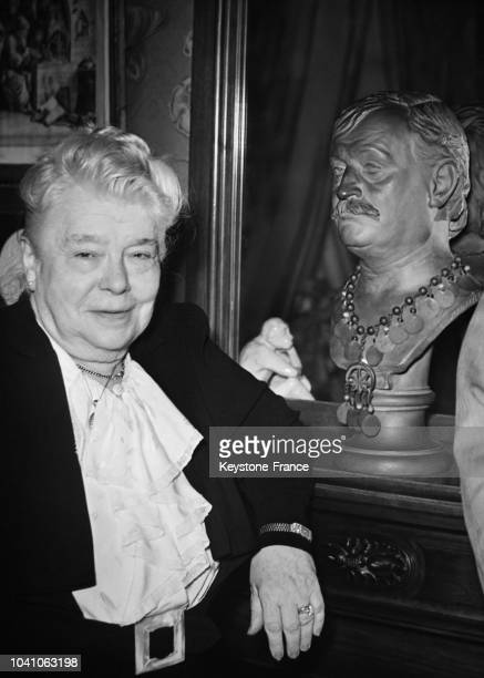 MarieJeanne Courteline photographiée à côté du buste de son marie Georges Courteline à Paris France circa 1960