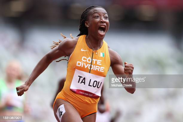 Marie-Josee Ta Lou of Team Ivory Coast reacts while competing during round one of the Women's 100m heats on day seven of the Tokyo 2020 Olympic Games...