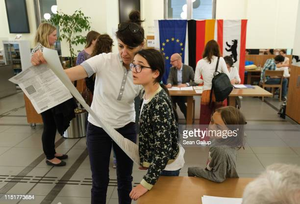 Marieke looks over an election ballot with her mother during voting at a polling station for European parliamentary elections on May 26 2019 in...