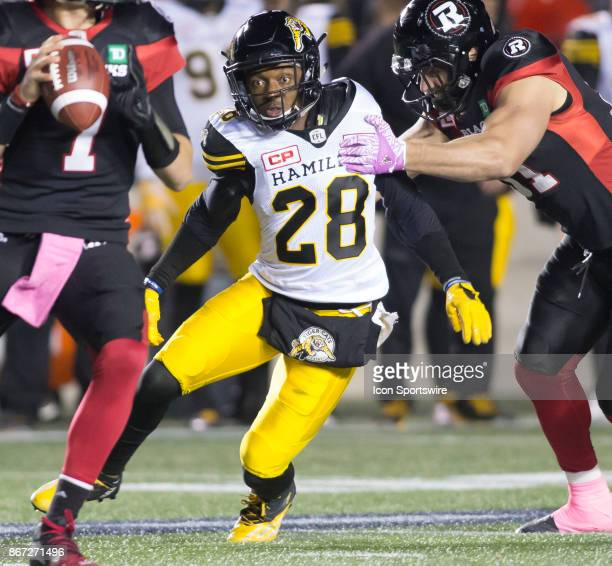 Mariel Cooper of the Hamilton TigerCats closes for an attempted sack on Trevor Harris of the Ottawa Redblacks in Canadian Football League play at TD...