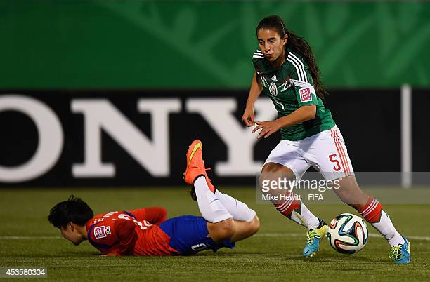 Mariel Gutierrez of Mexico gets the better of Lee Geummin of Korea Republic during the FIFA U20 Women's World Cup Canada 2014 Group D match between...