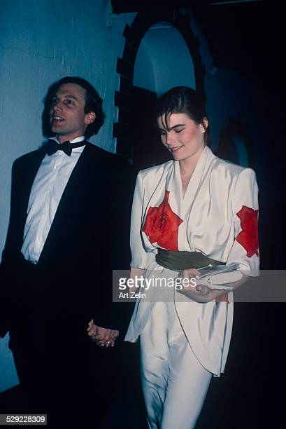 Mariel Hemingway with her husband Stephen Crisman holding hands at a formal event She is wearing a white sild top with red roses circa 1970 New York