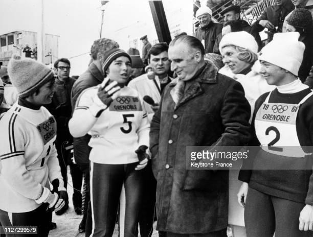 Marielle Goitschel qui vient de remporter la médaille d'or du slalom spécial discute avec le Premier ministre Georges Pompidou derrière lui Madame...