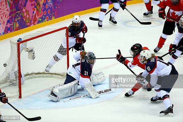 MariePhilip Poulin of Canada shoots and scores against Jessie Vetter of the United States late in the third period during the Ice Hockey Women's Gold...