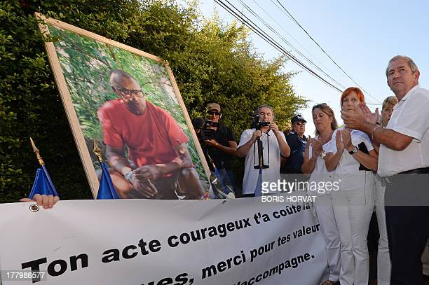Marignane's mayor Eric le Disses applauds as he pays tribute to Jacques Blondel at the end of a march in his memory on August 26, 2013 in Marignane,...