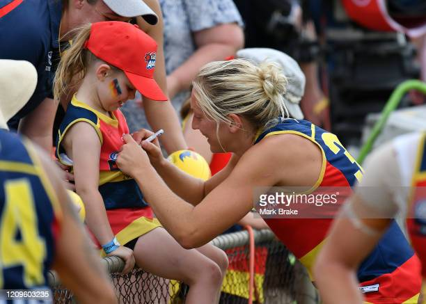 Marijana Rajcic of the Crows signs a young fans guernsey during the round four AFLW match between the Adelaide Crows and the Carlton Blues at...