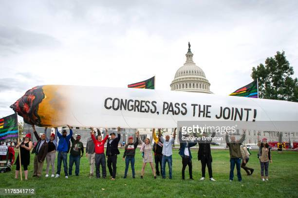 Marijuana activists hold up a 51foot inflatable joint during a rally at the US Capitol to call on Congress pass cannabis reform legislation on...