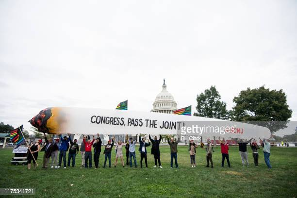 Marijuana activists hold up a 51-foot inflatable joint during a rally at the U.S. Capitol to call on Congress pass cannabis reform legislation on...