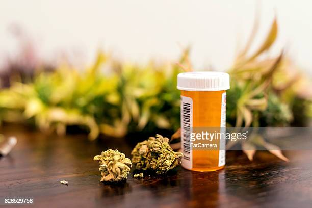 marijuana buds sitting next to prescription medicine bottle - dosis stock-fotos und bilder