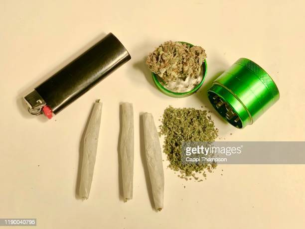 marijuana joints, ground cannabis, and grinder over white background - marijuana joint stock pictures, royalty-free photos & images