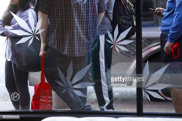 Marijuana leaf designs are displayed on a window as customers wait in line outside the MedMen dispensary in West Hollywood California US on Tuesday...