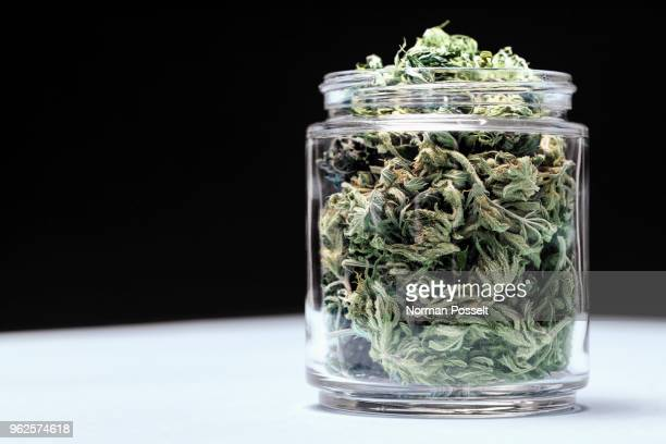 marijuana leaves in glass jar on table against black background - cannabis plant stock photos and pictures