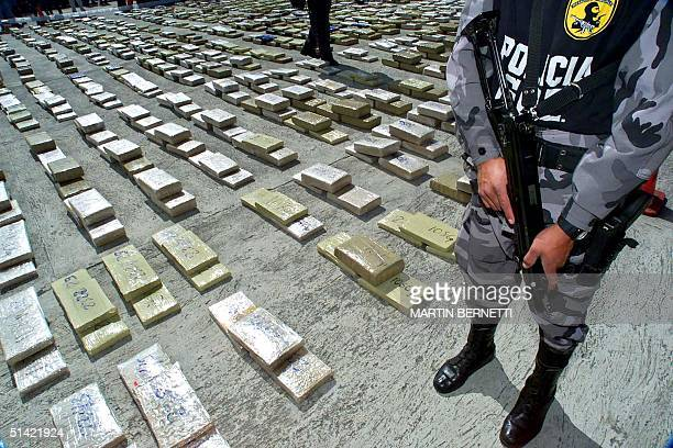 Marijuana packages are displayed by Bolivian police 28 November 2000 in Quito confiscated during Operation Galaxy Un policia antinarcotico vigila...