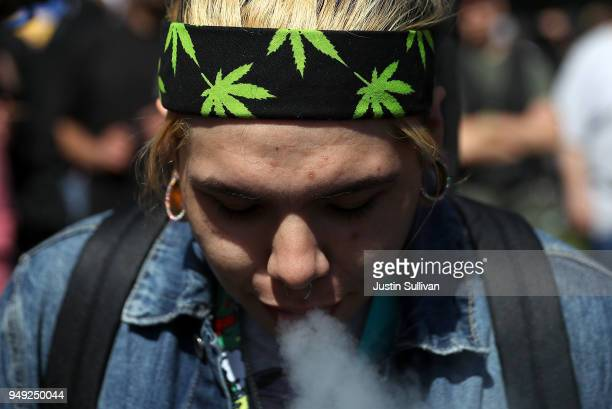 A marijuana user blows smoke after taking a hit from a bong during a 420 Day celebration on 'Hippie Hill' in Golden Gate Park on April 20 2018 in San...