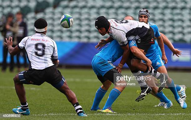 Marika Tokalauvere of Fiji offloads as he is tackled by Matteo Gabbianelli of Italy during the 2014 Junior World Championship match between Fiji and...