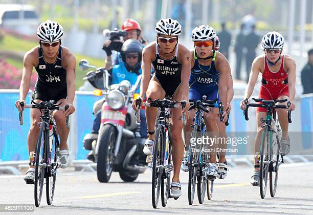 Mariko Adachi and Akane Tsuchihashi of Japan compete in the bike of the Women's Triathlon Individual during day one of the Guangzhou Asian Games on...