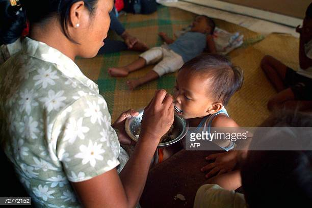 Marilou Mendoza feeds her toddler son at an evacuation camp in Guinobatan Albay province after seeking shelter after her house was ruined by Typhoon...