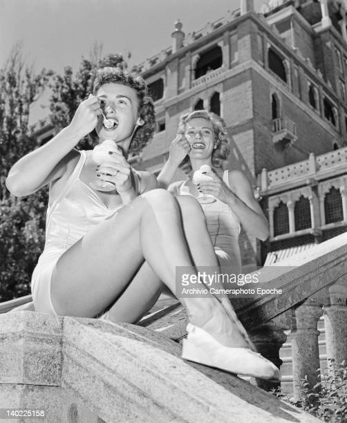 Marilyn Marsh and Charmaine Casey two of the Merriel Abbott Dancers eating ice creams in front of the Hotel Excelsior on the Venice Lido Italy 1950