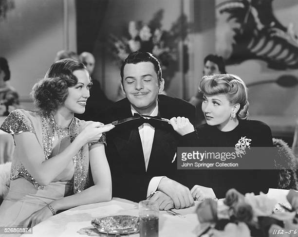Marilyn Marsh and Dixie Donegan Crane playfully hold butter knives to the throat of Buddy Crawford while at a restaurant in the 1941 comedic musical...