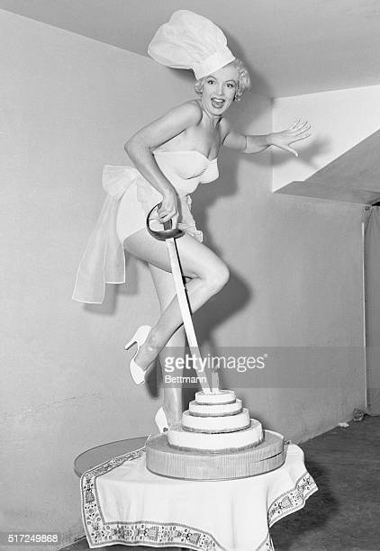 Marilyn Monroe 20th Century starlet who was recently selected Cheesecake Queen of 1952 looks as delicious as any confection as she plunges a sword...