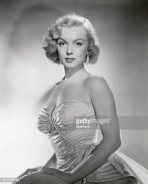 Marilyn Monroe American film star and sex image poses demurely in a strapless evening gown early in her career
