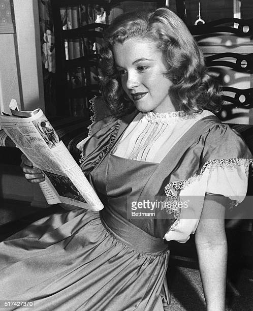 Marilyn Monroe at 21, reading a magazine and wearing a demure dress. Her hair is still long and undyed.