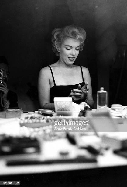 Marilyn Monroe at a makeup table getting ready for an event with photographer Sam Shaw's reflection visible in the mirror in 1955 in New York New York