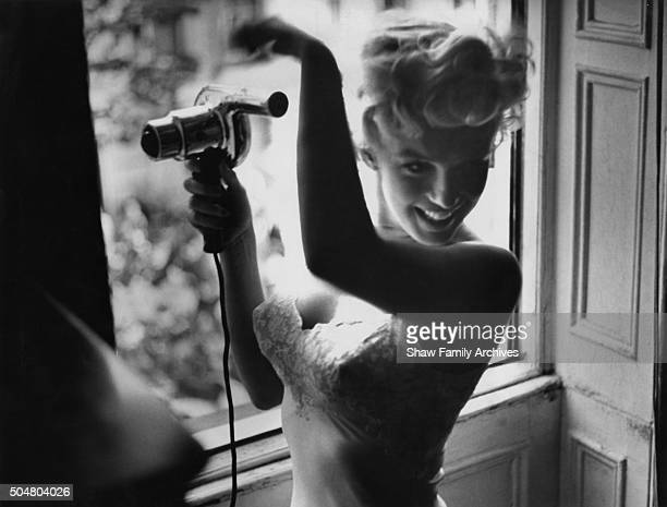 Marilyn Monroe blowdries her hair in front of an open window in 1954 during the filming of The Seven Year Itch in New York New York