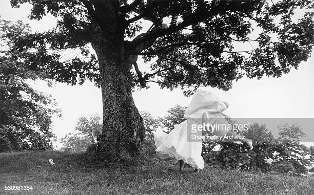 Marilyn Monroe dances barefoot in a field wearing a dress in 1957 in Amagansett New York