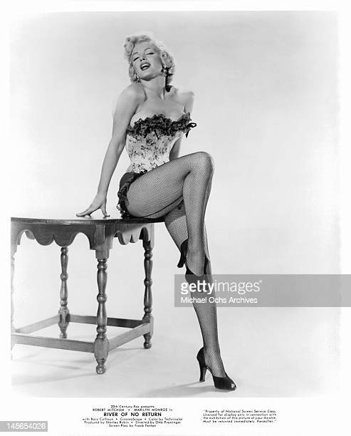 Marilyn Monroe dressed in a short showgirl outfit and leaning on a side table with her right leg up in a scene from the film 'River Of No Return' 1953