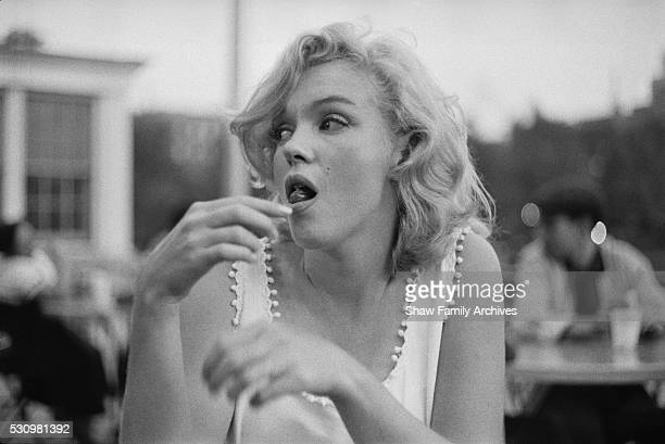 Marilyn Monroe eats a hot dog at an outdoor table in 1957 in New York New York