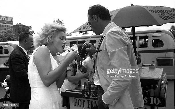 Marilyn Monroe eats a hot dog from a stand with her husband the playwright Arthur Miller in 1957 in New York New York