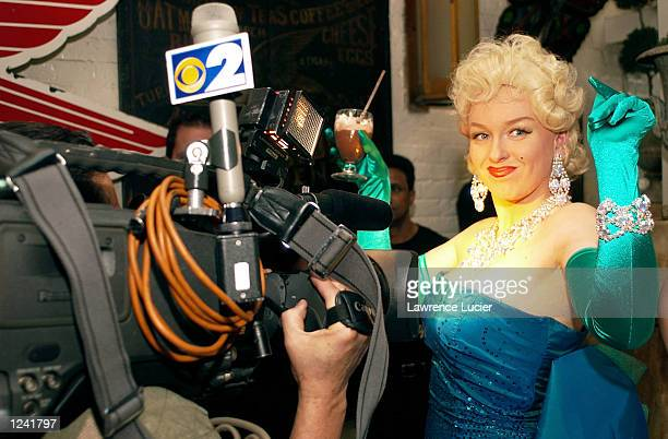 Marilyn Monroe fan dances for television cameras at a lookalike contest and seance at the restaurant Serendipity August 2 2002 in New York City...