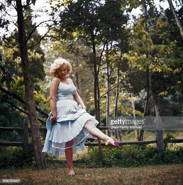 Marilyn Monroe frolicking in the grass barefoot in a blue dress with a pink flower between her toes in 1957 in Amagansett New York