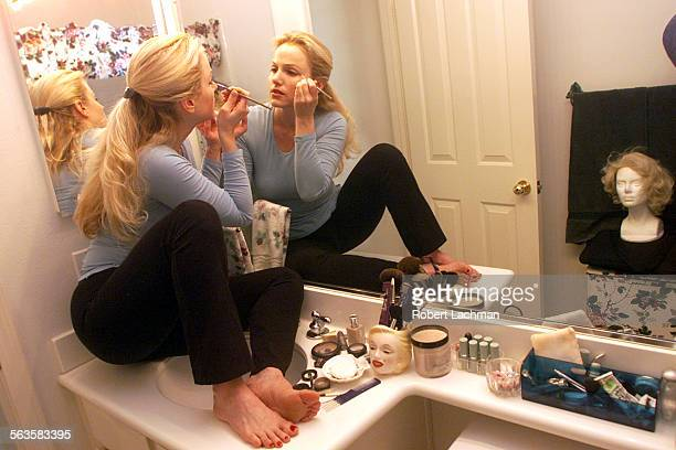 Marilyn Monroe impersonator Susan Griffiths puts her makeup on sitting on the bathroom sink of her Tustin home as she prepares for her appearance