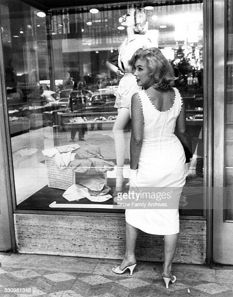 Marilyn Monroe in front of store window on Fifth Avenue in 1957 in New York New York