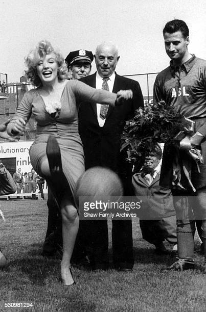 Marilyn Monroe kicks a soccer ball for the ceremonial kick off of a match between a combined Israeli Hapoel team and the American Soccer League Stars...